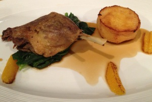 Confit Duck Leg with wilted spring greens and an orange reduction